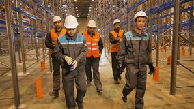 Σε αργή κίνηση εργαζόμενοι που τίθενται στα γάντια και τον περίπατο κατά μήκος της αποθήκης εμπορευμάτων απόθεμα βίντεο