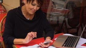 Σε αργή κίνηση ηλικίας θηλυκός δάσκαλος που εργάζεται σε υπαίθριο με το lap-top και το γράψιμο SMS από το smartphone απόθεμα βίντεο