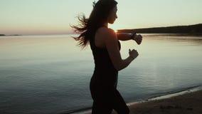Σε αργή κίνηση Θάλασσα στο ηλιοβασίλεμα Ενεργά τρεξίματα κοριτσιών κατά μήκος της ακτής απόθεμα βίντεο
