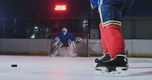 Σε αργή κίνηση λάκτισμα σφαιρών χόκεϋ κινηματογραφήσεων σε πρώτο πλάνο και πετώντας χιόνι Ένα θεαματικό χτύπημα φιλμ μικρού μήκους