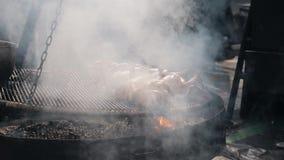 Σε αργή κίνηση μέσος πυροβολισμός ενός κρέατος κοτόπουλου σε μια σχάρα που καπνίζεται απόθεμα βίντεο