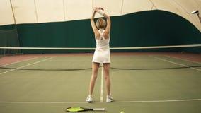 Σε αργή κίνηση μήκος σε πόδηα πίσω πλευρών ενός νέου αθλητικού θηλυκού τενίστα με τα κοντά ξανθά μαλλιά που φορούν άσπρο sportswe φιλμ μικρού μήκους