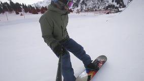 Σε αργή κίνηση μήκος σε πόδηα του snowboarder που κάνει το υψηλό άλμα στο βουνό απόθεμα βίντεο