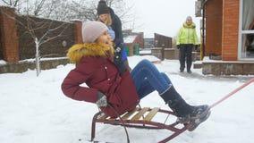 Σε αργή κίνηση μήκος σε πόδηα της ευτυχούς οικογένειας που οδηγά και που παίζει στο κατώφλι σπιτιών που καλύπτεται με το χιόνι φιλμ μικρού μήκους