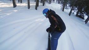 Σε αργή κίνηση μήκος σε πόδηα της οδήγησης ατόμων snowboarder μέσω του δάσους απόθεμα βίντεο
