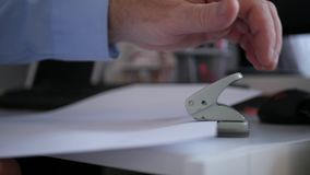 Σε αργή κίνηση με την εργασία γραφείων επιχειρηματιών που χρησιμοποιεί έναν Τύπο τρυπανιών για τα έγγραφα απόθεμα βίντεο