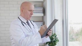 Σε αργή κίνηση με το γιατρό που γράφει μια ιατρική συνταγή στο εσωτερικό του δωματίου ιατρείων απόθεμα βίντεο