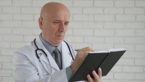 Σε αργή κίνηση με το σοβαρό γιατρό που γράφει τις ιατρικές σημειώσεις στην ημερήσια διάταξη σε Hos [ital απόθεμα βίντεο