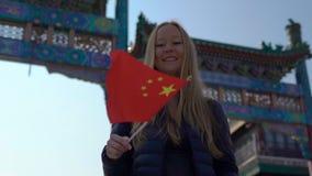 Σε αργή κίνηση μιας νέας γυναίκας bloger που κρατά μια μικρή κινεζική σημαία στεμένος στη λεωφόρο κεντρικών δρόμων Quinmen Απαγορ απόθεμα βίντεο