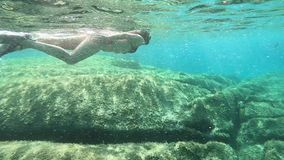 Σε αργή κίνηση μιας όμορφης νέας γυναίκας σε ένα μαύρο μπικίνι που λαμβάνεται από την υποβρύχια κολύμβηση στο μπλε νερό με τη μάσ φιλμ μικρού μήκους