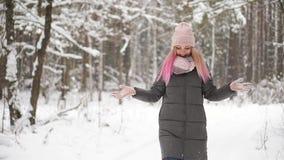 Σε αργή κίνηση, μια γυναίκα σε ένα καπέλο σακακιών και μαντίλι το χειμώνα στο δασικό χιόνι εκμετάλλευσης στα χέρια της και φύσηγμ απόθεμα βίντεο