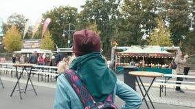 Σε αργή κίνηση νέος καυκάσιος τουρίστας κοριτσιών σε μια μπλε ζακέτα και ένα σακίδιο πλάτης πίσω από τους περιπάτους γύρω από την απόθεμα βίντεο