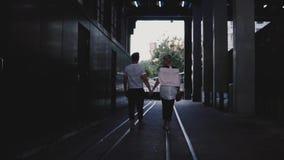 Σε αργή κίνηση πίσω ευτυχές ρομαντικό ζεύγος άποψης που περπατά μαζί να κρατήσει τα χέρια στις ράγες κάτω από τη σκοτεινή γέφυρα  φιλμ μικρού μήκους