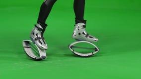 Σε αργή κίνηση παπούτσια αλμάτων kangoo κινηματογραφήσεων σε πρώτο πλάνο στο πράσινο βασικό κλίμα χρώματος απόθεμα βίντεο