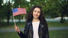 Σε αργή κίνηση πορτρέτο ευτυχής αμερικανική κυματίζοντας σημαία τουριστών των Ηνωμένων Πολιτειών, της εξέτασης τη κάμερα και του  απόθεμα βίντεο