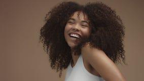 Σε αργή κίνηση πορτρέτο κινηματογραφήσεων σε πρώτο πλάνο της μαύρης γυναίκας laughin με τη σγουρή τρίχα απόθεμα βίντεο
