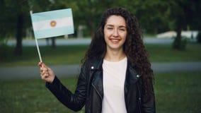 Σε αργή κίνηση πορτρέτο της ελκυστικής αργεντινής γυναίκας που κυματίζει την επίσημη σημαία της Αργεντινής, της εξέτασης τη κάμερ απόθεμα βίντεο