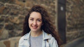 Σε αργή κίνηση πορτρέτο της ελκυστικής νέας γυναίκας στο σακάκι τζιν που εξετάζει τη κάμερα και τη στάση χαμόγελου ενάντια στον τ απόθεμα βίντεο