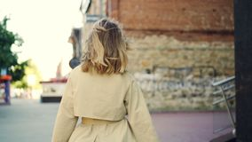 Σε αργή κίνηση πορτρέτο της ευτυχούς νέας κυρίας στο κομψό ένδυμα που περπατά στην οδό, που χαμογελά και που εξετάζει τη κάμερα απόθεμα βίντεο