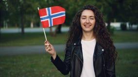 Σε αργή κίνηση πορτρέτο της εύθυμης κυρίας στον περιστασιακό ιματισμό που κυματίζει τη νορβηγική σημαία, την εξέταση τη κάμερα κα απόθεμα βίντεο