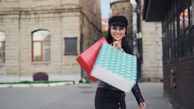 Σε αργή κίνηση πορτρέτο της όμορφης ασιατικής γυναίκας που γυρίζει στη κάμερα και το περπάτημα χαμόγελου με τις τσάντες εγγράφου  φιλμ μικρού μήκους