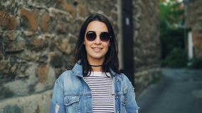 Σε αργή κίνηση πορτρέτο της όμορφης νέας γυναίκας στα γυαλιά ηλίου και το σακάκι τζιν που στέκεται υπαίθρια με τους τουβλότοιχους απόθεμα βίντεο