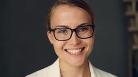 Σε αργή κίνηση πορτρέτο της όμορφης νέας επιχειρηματία που φορά τα μοντέρνα γυαλιά που εξετάζουν τη κάμερα και το χαμόγελο _ απόθεμα βίντεο