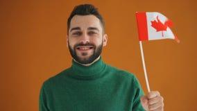 Σε αργή κίνηση πορτρέτο του γενειοφόρου νέου σπουδαστή με το καναδικό χαμόγελο σημαιών απόθεμα βίντεο