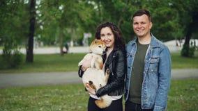 Σε αργή κίνηση πορτρέτο του ελκυστικού νέου brunette γυναικών που κρατά το σκυλί της στεμένος στο πάρκο με το φίλο Ευτυχής φιλμ μικρού μήκους