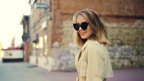 Σε αργή κίνηση πορτρέτο του ελκυστικού ξανθού περπατήματος κοριτσιών στην οδό, του χαμόγελου και της εξέτασης τη κάμερα εύθυμοι ά φιλμ μικρού μήκους