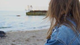 Σε αργή κίνηση πορτρέτο του εύθυμου κοριτσιού που που θέτει στη κάμερα και το χαριτωμένο γέλιο καθμένος στην παραλία ενάντια στην φιλμ μικρού μήκους