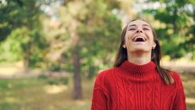 Σε αργή κίνηση πορτρέτο του εύθυμου κοριτσιού στο θερμό πουλόβερ που στέκεται στο πάρκο με το ευτυχές χαμόγελο, που γελά και που  απόθεμα βίντεο