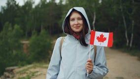 Σε αργή κίνηση πορτρέτο του θηλυκού ταξιδιωτικού όμορφου κοριτσιού που κρατά την καναδική σημαία, που χαμογελά και που εξετάζει τ απόθεμα βίντεο