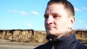 Σε αργή κίνηση πορτρέτο του νεαρού άνδρα που απολαμβάνουν την ηλιόλουστη ημέρα στη φύση στο χειμώνα απόθεμα βίντεο