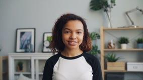 Σε αργή κίνηση πορτρέτο του χαριτωμένου κοριτσιού αφροαμερικάνων που εξετάζει τη κάμερα με το χαμόγελο απόθεμα βίντεο