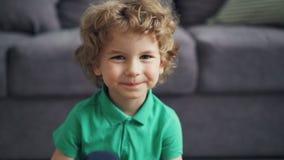 Σε αργή κίνηση πορτρέτο του χαριτωμένου μικρού παιδιού που εξετάζει τη κάμερα και που χαμογελά στο σπίτι απόθεμα βίντεο