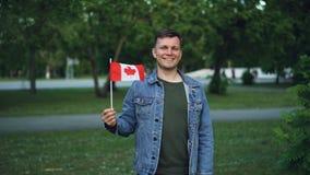 Σε αργή κίνηση πορτρέτο του όμορφου αρσενικού ταξιδιωτικού εύθυμου τύπου που κυματίζει την καναδική σημαία, την εξέταση τη κάμερα απόθεμα βίντεο