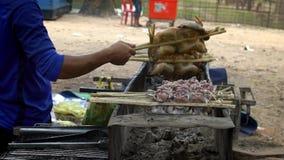 Σε αργή κίνηση προμηθευτής που μαγειρεύει το καμποτζιανό κοτόπουλο στην οδό αγοράς σχαρών φιλμ μικρού μήκους
