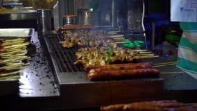 Σε αργή κίνηση προμηθευτής που μαγειρεύει το ταϊβανικό κοτόπουλο στο ραβδί Οδός αγοράς νύχτας απόθεμα βίντεο