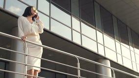 Σε αργή κίνηση πυροβολισμός μιας ελκυστικής επιχειρησιακής γυναίκας brunette που φορούν την άσπρη μπλούζα και της φούστας που χρη απόθεμα βίντεο