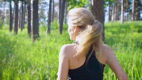 Σε αργή κίνηση πυροβολισμός μιας νέας ξανθής γυναίκας σε ένα αθλητικό κοστούμι, που τρέχει ενεργά μέσω του πάρκου κατά τη διάρκει απόθεμα βίντεο