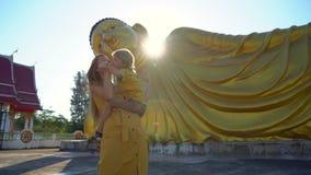 Σε αργή κίνηση πυροβολισμός μιας νέων γυναίκας και της λίγος γιος που έχει τη διασκέδαση μπροστά από ένα άγαλμα να βρεθεί Βούδας  απόθεμα βίντεο