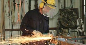 Σε αργή κίνηση πυροβολισμός ενός αλέθοντας μετάλλου εργαζομένων που χρησιμοποιεί έναν μύλο μετάλλων φιλμ μικρού μήκους