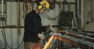 Σε αργή κίνηση πυροβολισμός ενός αλέθοντας μετάλλου εργαζομένων που χρησιμοποιεί έναν μύλο μετάλλων απόθεμα βίντεο