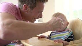 Σε αργή κίνηση πυροβολισμός του ταΐζοντας αγοράκι πατέρων στην υψηλή έδρα φιλμ μικρού μήκους