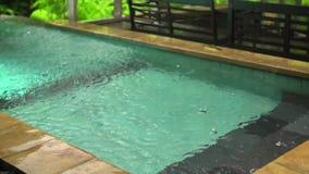 Σε αργή κίνηση σταγόνες βροχής που περιέρχονται στο μπλε νερό της ανοικτής πισίνας, διάστημα αντιγράφων απόθεμα βίντεο