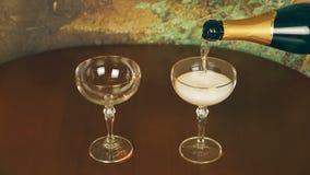 Σε αργή κίνηση στενή επάνω χύνοντας σαμπάνια λαμπιρίζοντας κρασιού στο γυαλί δύο στον ξύλινο πίνακα Ρομαντική ατμόσφαιρα βραδιού απόθεμα βίντεο