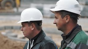Σε αργή κίνηση σχεδιάγραμμα δύο άτομα στα άσπρα σκληρά καπέλα στο τράβηγμα εστίασης εργοτάξιων απόθεμα βίντεο