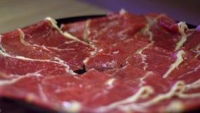 Σε αργή κίνηση της ακατέργαστης λαβής κρέατος βόειου κρέατος με chopsticks Κινεζικό hotpot στο Πεκίνο απόθεμα βίντεο