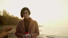 Σε αργή κίνηση της ασιατικής γυναίκας στο παλτό και eyeglasses που περπατούν στην παραλία στο ηλιοβασίλεμα φιλμ μικρού μήκους